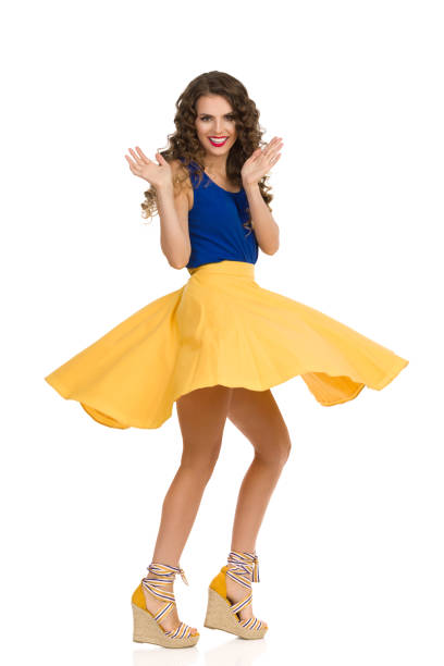 Beautiful young woman in circle cut yellow skirt and platform high heels shoes is dancing and spinning. Full length studio shot isolated on white.