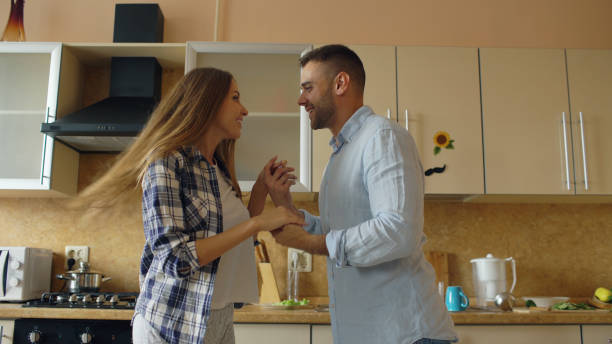 Attractive young joyful couple have fun dancing while cooking in the kitchen at home in the morining