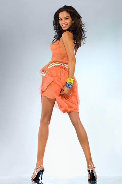 Beautiful young woman dancing in orange dress