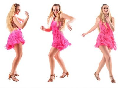 Carefree joyful smiling woman dancing in pink fringed dress. Side view. Full body length portrait isolated on white studio background.